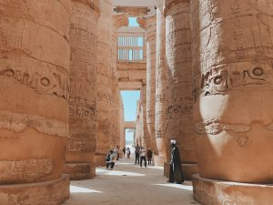 people standing near brown pillars